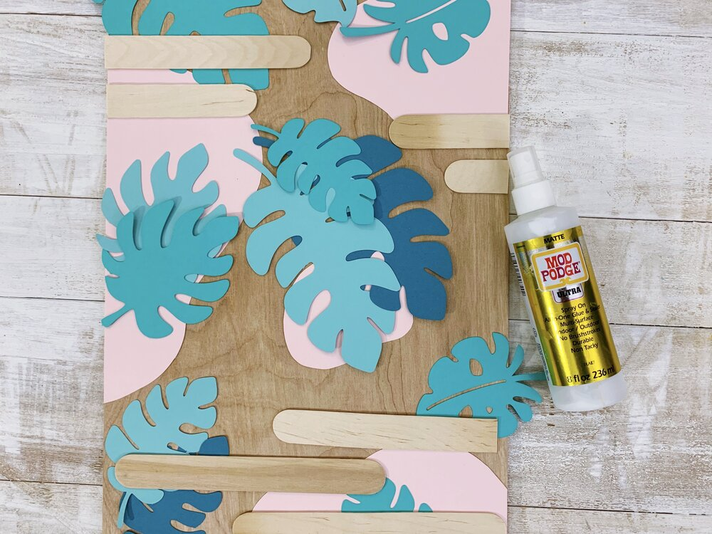 Golden Girls Inspired DIY Tropical Graphic Wall Art using Mod Podge Ultra  #wallart #plywood #papercrafts #paper #modpodge #plaidcrafts #modpodgeultra #thegoldengirls #summercrafts #summer #homedecor #paperleaves #tropicalvibes #tropicalart #smallspaces #apartmenttherapy #crciutmaker #cricutcrafts #decoupage #monstera #monsteraleaves #monsteraplant #palmleaf #tropicalplant