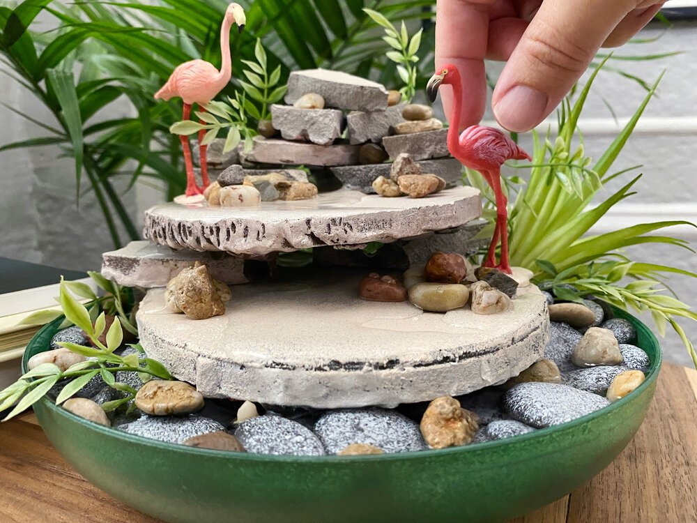 Create a relaxing tabletop fountain with Flex Seal and a quick trip to Dollar Tree!  #diyfountain #dollartreecrafts #diydollartree #fountain #indoorgarden #indoorfountain #homedecor #zen #relaxing #homedecordiy #cozyapartment #flexsealcolor #flexsealspray #flexglue #stressrelief #waterpump #waterfeature #dollartreegarden #homeofficedecor #flamingoministures #flamingodiy #gardendiy #fountainidea #waterfountain #rocks #pebbles #calm #calming